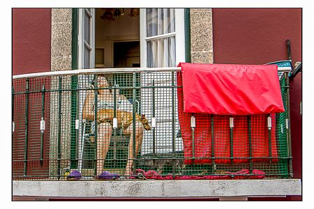 Mulher e cachorro dormindo na sacada em Porto